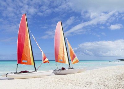 Two catamarans with its colorful sails wide open on Cuban white